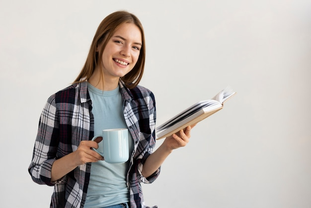 Femme lisant un livre tout en tenant une tasse de café Photo gratuit