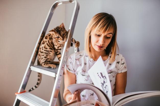Femme lit un livre tandis que le chat du bengale se dresse sur l'échelle derrière elle Photo gratuit