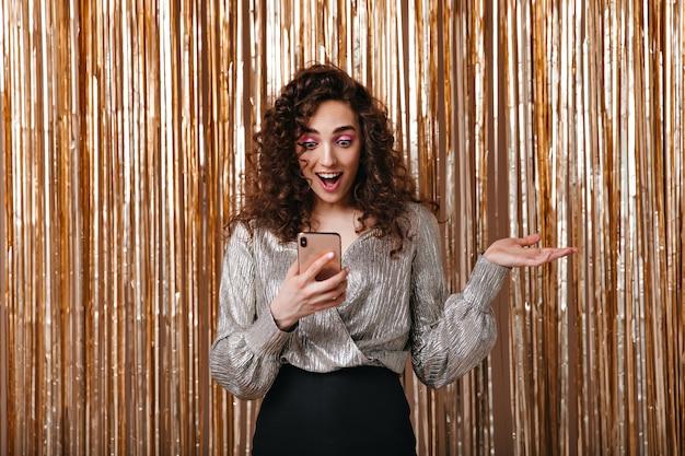 Femme Lit Le Message Au Téléphone Et Posant Surpris Sur Fond Doré Photo gratuit