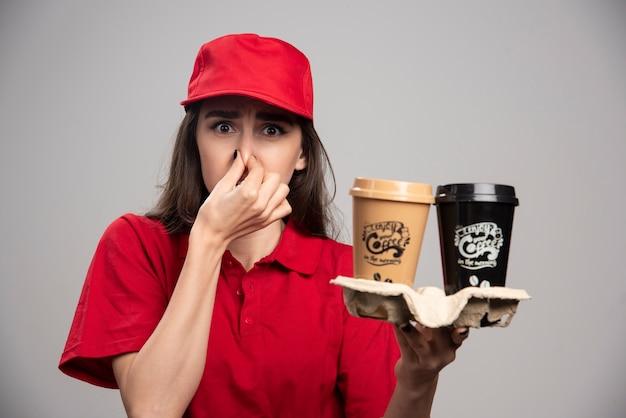 Femme De Livraison En Uniforme Rouge Tenant Son Nez Fermement à Cause De L'odeur. Photo gratuit