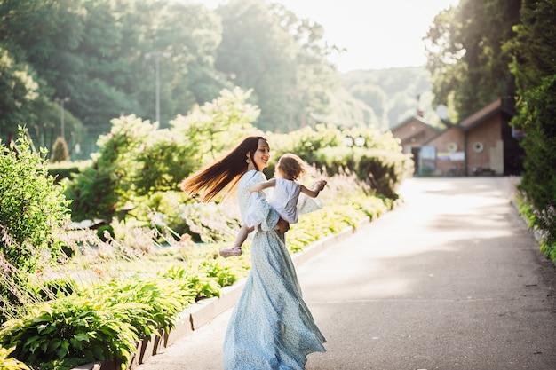 Femme En Longue Robe Bleue Tourbillonne Avec Sa Petite Fille Sur Le Chemin De La Chaussée Photo gratuit