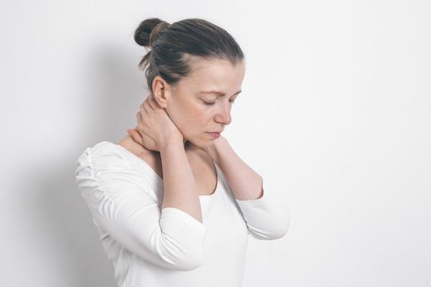 Une femme lui tient la main par le cou. douleur à la colonne vertébrale fatigue. Photo Premium