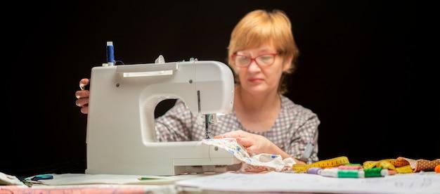 Femme à lunettes à l'aide d'une machine à coudre ou à enfiler sur un fond sombre Photo Premium