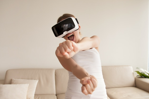 Femme en lunettes de réalité virtuelle bénéficiant de jeux en 3d à la maison Photo gratuit