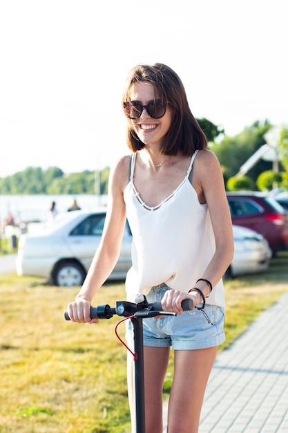 Femme, lunettes soleil, trottinette Photo gratuit