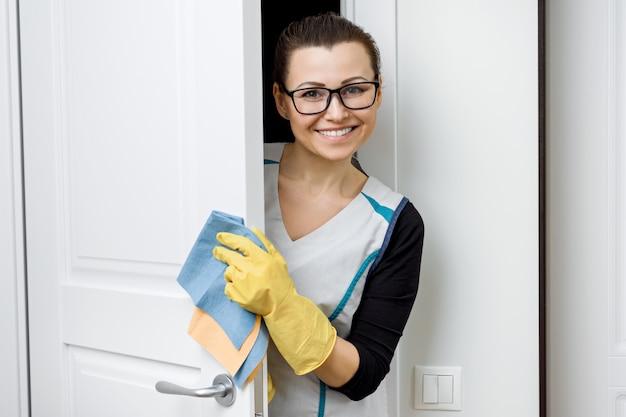 Femme à lunettes et tablier pour le nettoyage des gants en caoutchouc avec des détergents Photo Premium