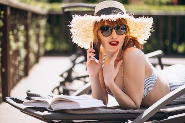 Femme en maillot de bain allongée sur un lit et lisant un livre Photo gratuit