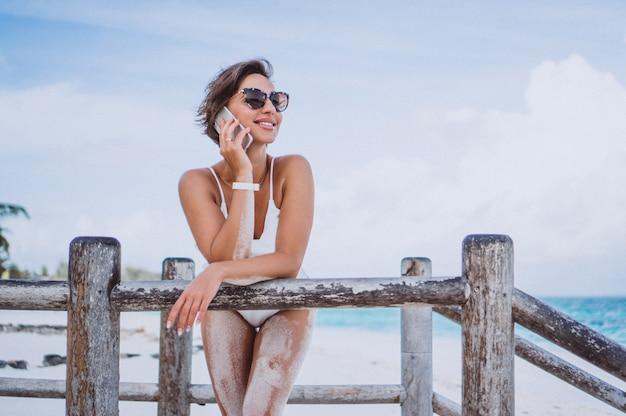 Femme en maillot de bain blanc au bord de l'océan à l'aide d'un téléphone Photo gratuit