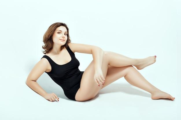 Femme En Maillot De Bain Noir. Elle S'assoit De Son Côté Et Croisa Les Jambes Photo Premium