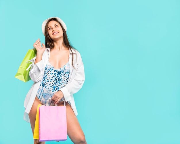 Femme en maillot de bain avec des sacs Photo gratuit