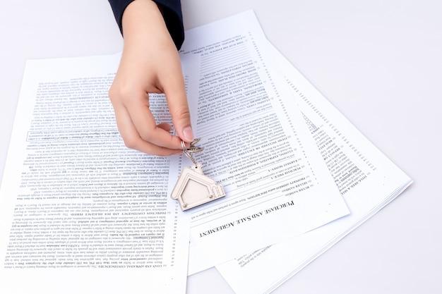 Femme main et clé de la maison. contrat signé et clés de la propriété avec documents. concept pour les affaires immobilières. Photo Premium