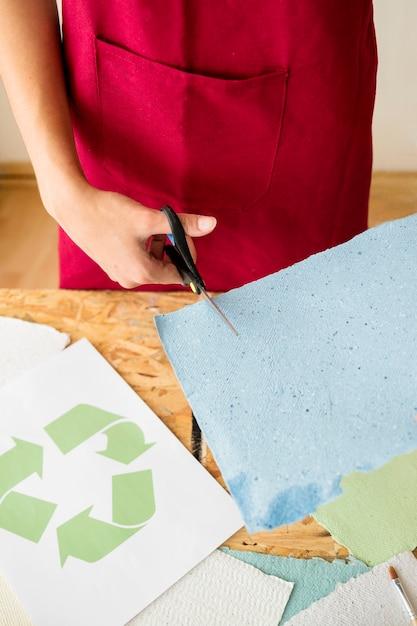 Femme main coupe papier bleu avec des ciseaux Photo gratuit
