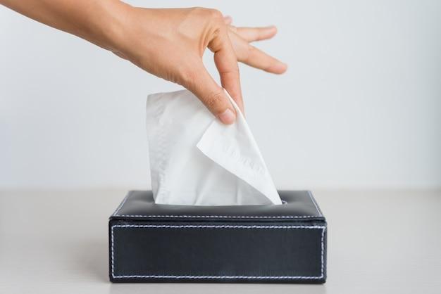 Femme main cueillette de papier de soie blanc de boîte à mouchoirs. Photo Premium