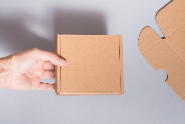 Femme Main Holns Boîte En Carton Marron Sur Fond Gris Photo Premium