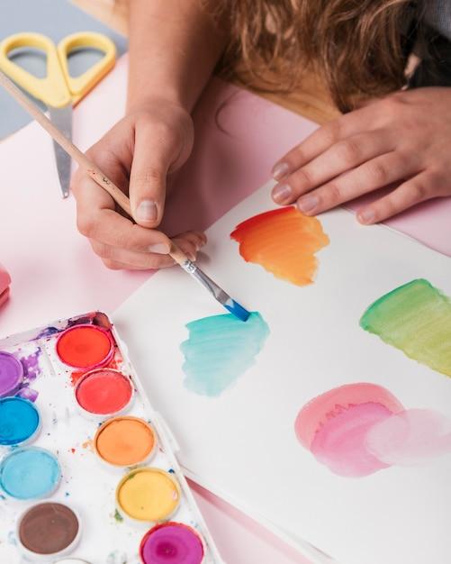 Femme main peinture dessin abstrait sur papier blanc à l'aide d'aquarelle Photo gratuit