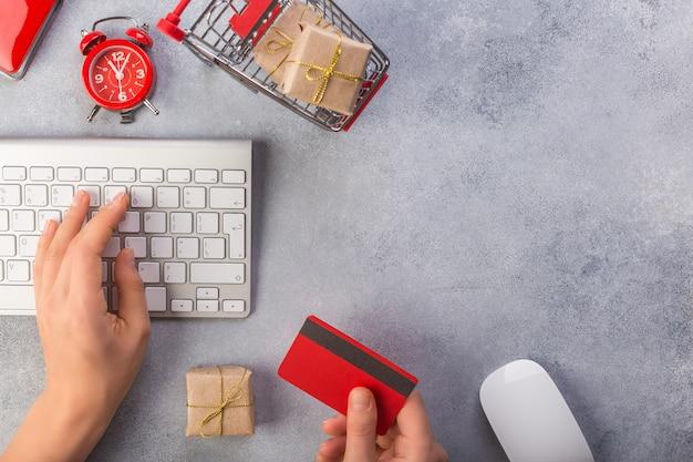 Femme main prend la carte de crédit, l'autre main est sur le clavier Photo Premium