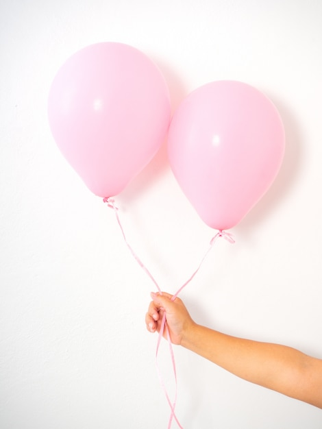 Femme main tenant des ballons roses Photo Premium
