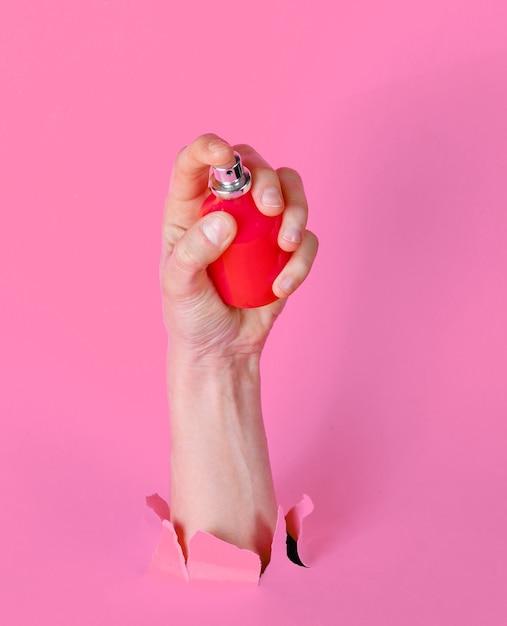 Femme Main Tenant Une Bouteille De Parfum à Travers Du Papier Rose Déchiré. Concept De Mode Minimaliste Photo Premium