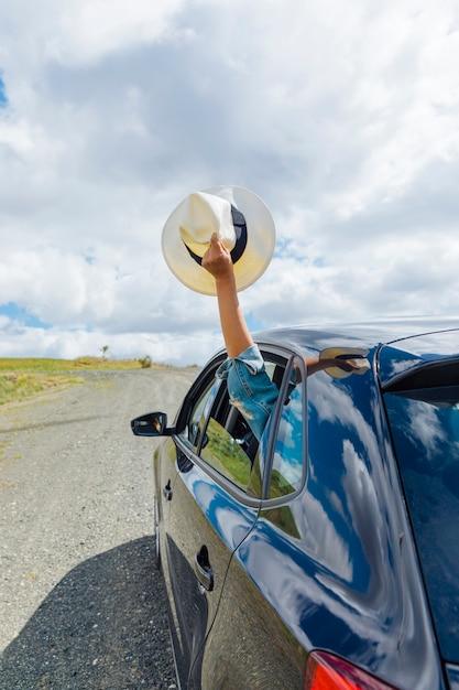 Femme main tenant un chapeau par la fenêtre de la voiture Photo gratuit