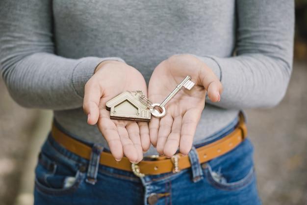 Femme main tenant la clé de la maison, concept d'agent immobilier Photo Premium