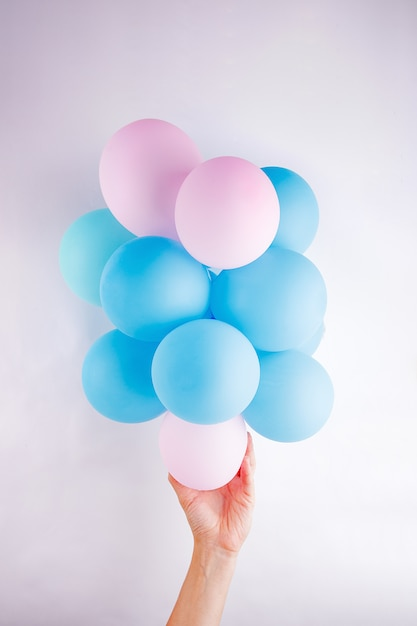 Femme main tenant un ensemble de petites ballons roses et bleus lika un nuage sur fond blanc Photo Premium