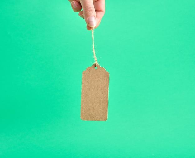 Femme main tenant une étiquette vierge papier brun sur une corde Photo Premium