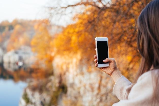 Femme main tenant un téléphone, écran noir Photo gratuit
