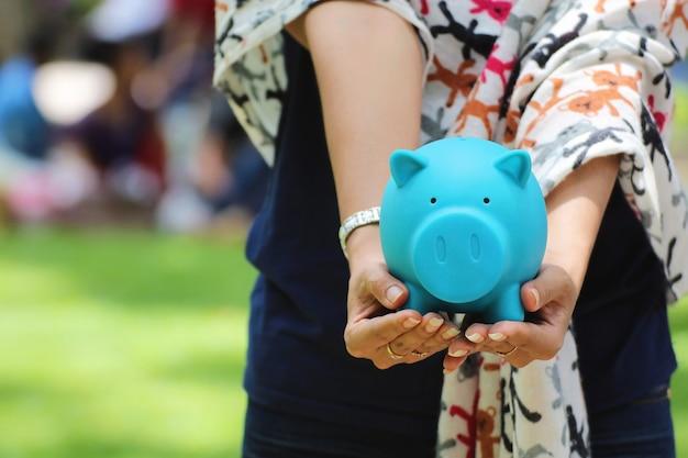 Femme Main Tenant Une Tirelire Bleue, Idées D'investissement Financier Ou Bancaire Photo Premium