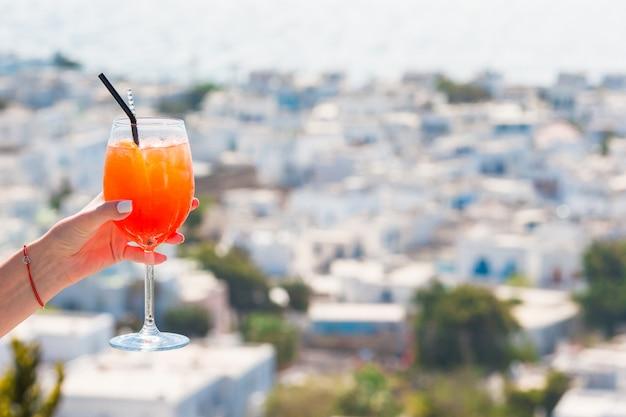 Femme main tenant le verre avec l'alcool spritz aperol boire fond dans le beau vieux mykonos en grèce Photo Premium
