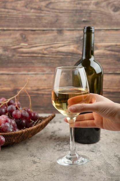 Femme Main Tenant Un Verre De Vin Blanc Sur Table En Marbre. Photo gratuit
