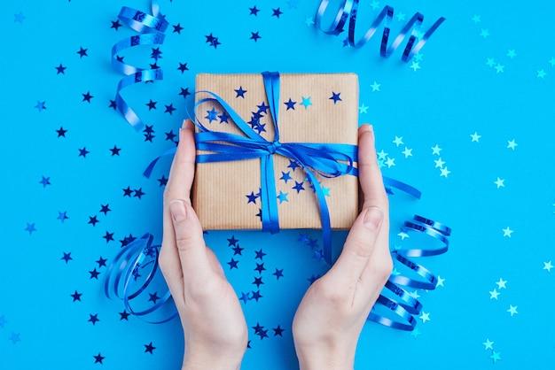 Femme main tenir une boîte cadeau emballée dans du papier kraft Photo Premium