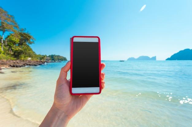 Femme Main Tenir Un Téléphone Mobile Blanc Avec Une Belle Mer Douce Et Un Ciel Bleu Photo Premium