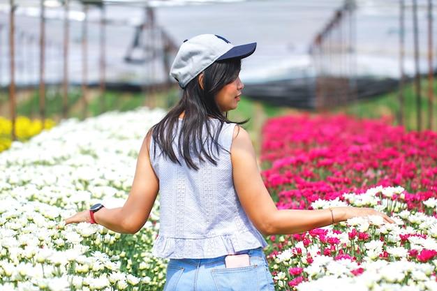Femme main touchant des fleurs dans un jardin Photo Premium