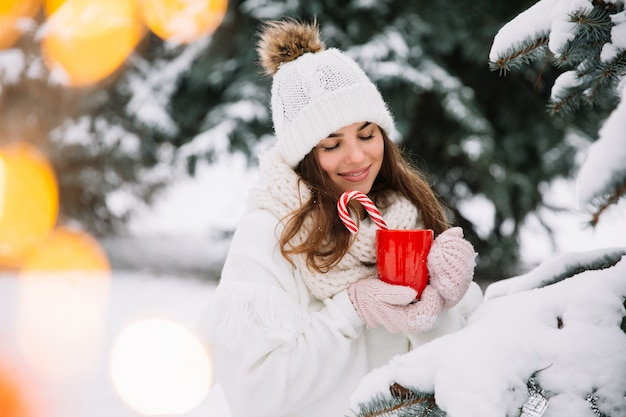 Femme Mains Dans Les Gants Tenant Une Tasse Confortable Avec Du Cacao Chaud, Du Thé Ou Du Café Et Une Canne En Bonbon. Photo Premium