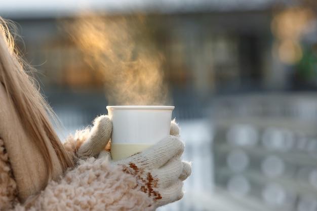 Femme Mains Dans Des Mitaines Blanches Tenant Une Tasse Blanche Fumante De Café Chaud Ou De Thé En Froide Journée Ensoleillée D'hiver Photo Premium