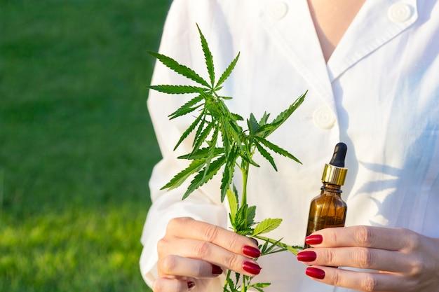Femme, mains, manteau, tenue, branche, cannabis, cinq, doigts, bouteille, verre, bouteille Photo Premium