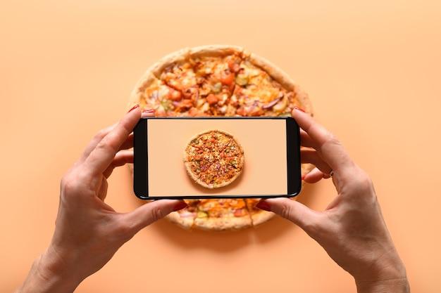 Femme Mains Prend La Photographie De Pizza Végétalienne Italienne Avec Tomate, Mozzarella, Sauce Photo Premium