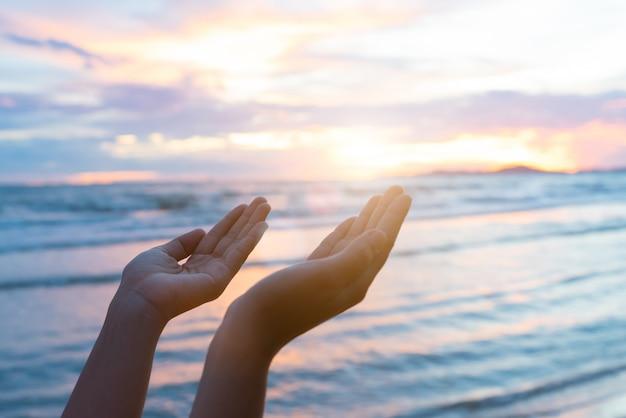 Femme mains priant pour la bénédiction de dieu pendant le coucher du soleil. concept de l'espoir. Photo Premium