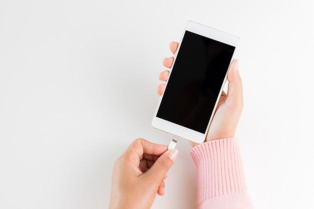 Femme mains reliant le chargeur au smartphone sur fond de tableau blanc Photo Premium