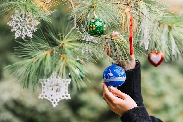 Femme mains suspendus des jouets de noël sur brindille en forêt Photo gratuit