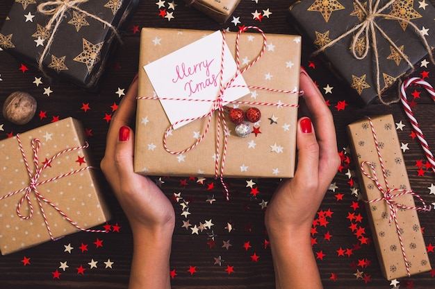 Femme mains tenant la boîte de cadeau de vacances de noël avec carte postale joyeux noël sur la table de fête décorée Photo gratuit