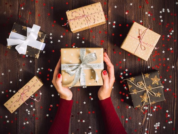 Femme mains tenant la boîte de cadeau de vacances de noël sur la table de fête décorée Photo gratuit