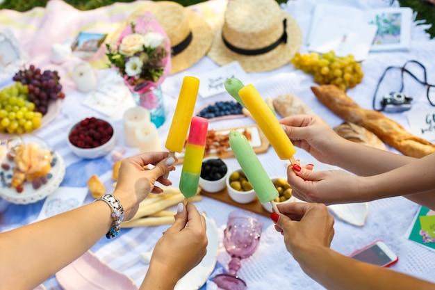 Femme mains tenir des bâtons de glace colorés au pique-nique estival. week-end d'été Photo Premium
