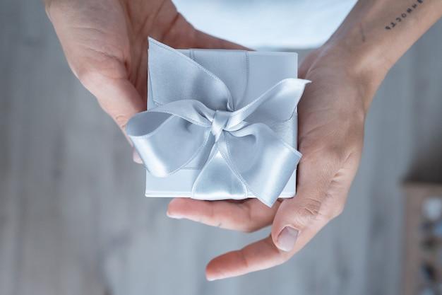 Femme, mains, tenue, boîte cadeau, à, arc blanc, gros plan Photo gratuit