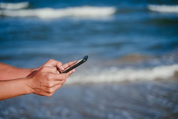 Femme, Mains, Tenue, Téléphone Portable, Plage Photo Premium