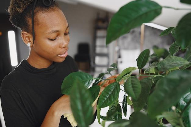 Femme à La Maison. Fille Dans Un Pull Noir. Femme Africaine Utilise Le Chiffon. Personne Avec Pot De Fleurs. Photo gratuit
