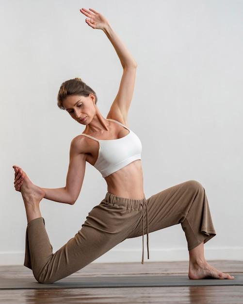 Femme à La Maison Pratiquant Le Yoga Sur Tapis Photo gratuit