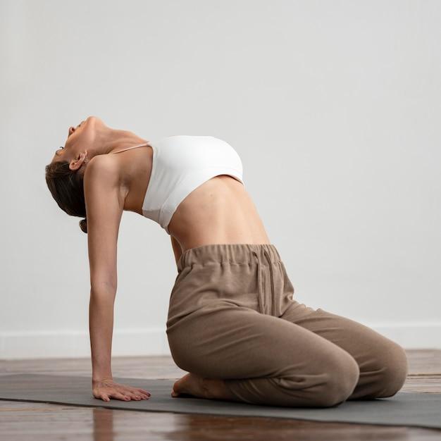 Femme à La Maison Pratiquant Le Yoga Photo gratuit