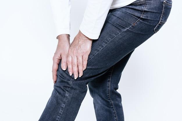 Une femme a mal au genou, elle fait un massage. Photo Premium