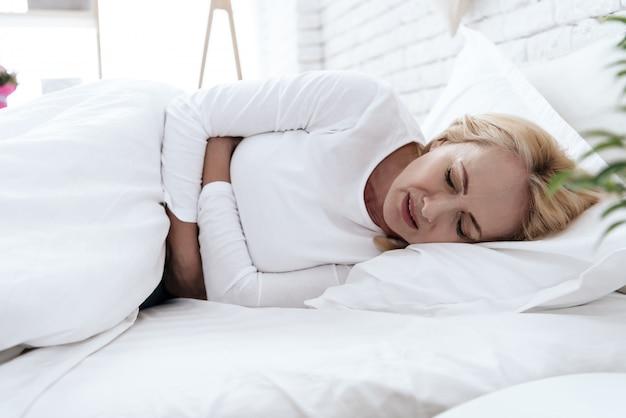 La femme a mal au ventre, couchée dans son lit. Photo Premium